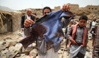 A man displays the bloodied shirt of a victim at the rubble of houses destroyed by an air strike in the Okash village near Sanaa