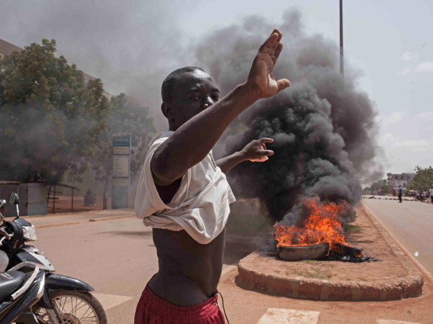 A Burkina Faso protestor gestures in front of burning tires as he and others take to the streets in the city of Ouagadougou, Burkina Faso, Thursday, Sept. 17, 2015. While gunfire rang out in the streets, Burkina Fasoís military took to the airwaves Thursday to declare it now controls the West African country, confirming that a coup had taken place just weeks before elections. (AP Photo/Theo Renaut)