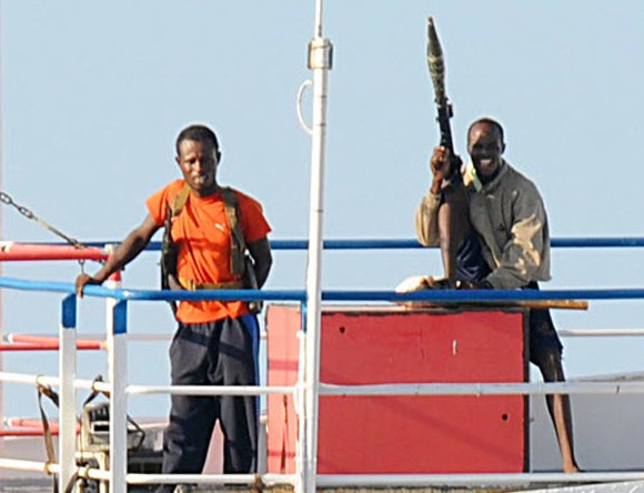 In this photo released by the US Navy on November 10, 2008, the crew of the hijacked merchant vessel MV Faina stand on the deck on November 9 after a US Navy request to check on their health and welfare, at sea off the coast of Somalia. The Belize-flagged cargo ship owned and operated by Kaalbye Shipping, Ukraine, was seized by pirates September 25 and forced to proceed to anchorage off the Somali Coast. The ship is carrying a cargo of Ukrainian T-72 tanks and related military equipment. MCS2 Jason R. Zalasky/ RELEASED RESTRICTED TO EDITTORIAL USE = GETTY OUT =