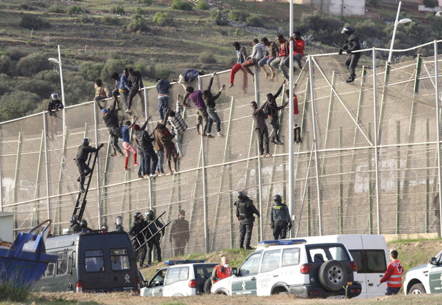 Migranti cercano di scavalcare la barriera di protezione a Ceuta