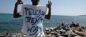 "A migrant shouts a slogan as he wears a Tee Shirt with the message, ""Open The Way"" as he stands on the seawall at the Saint Ludovic border crossing on the Mediterranean Sea between Vintimille, Italy and Menton, France, June 14, 2015. On Saturday, some 200 migrants, principally from Eritrea and Sudan who attempted to cross the border, were blocked by Italian police and French gendarmes.   REUTERS/Eric Gaillard"
