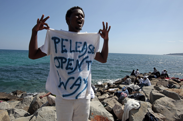 """A migrant shouts a slogan as he wears a Tee Shirt with the message, """"Open The Way"""" as he stands on the seawall at the Saint Ludovic border crossing on the Mediterranean Sea between Vintimille, Italy and Menton, France, June 14, 2015. On Saturday, some 200 migrants, principally from Eritrea and Sudan who attempted to cross the border, were blocked by Italian police and French gendarmes.   REUTERS/Eric Gaillard"""
