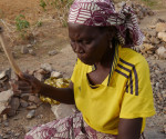 In this photo taken on Wednesday, June 15, 2016, a women rock-crusher hits rocks with a hammer in a quarry at Maroua, Cameroon. In a northern Cameroon town menaced by food insecurity and suicide bombers, women as old as 85 are spending long, grueling days crushing rocks into gravel to earn a living. (AP Photo/Joel Kouam)
