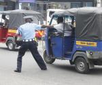 Agente del traffico alle prese con il conducente di un tuk-tuk che cerca di scappare