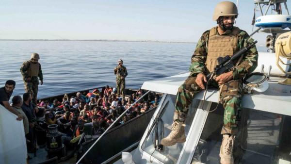 Guardia costiera libica con un gruppo di migranti