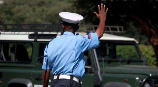 Un agente della polizia stradale del Kenya ferma un automobilista per un controllo