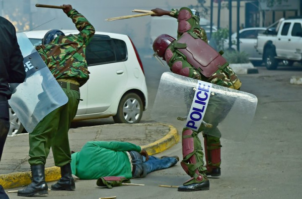 A picture taken on May 16, 2016 in Nairobi shows Kenyan riot police beating an unresponsive fallen protester with wooden sticks until they break and repeatedly kick him several times. The incident has caused Kenya's police chief to order an internal investigation into the incident and other reported incidents of police brutality on the day. Police fired tear gas and beat opposition demonstrators with truncheons on May 16 to stop them storming the offices of the electoral commission in Nairobi as they demanded new commissioners to be named ahead of elections due in August 2017. / AFP / CARL DE SOUZA (Photo credit should read CARL DE SOUZA/AFP/Getty Images)